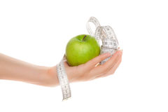 Woman's hands holding apple with measuring tape Royalty Free Stock Photography
