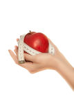 Woman's hands holding apple with measuring tape Stock Photo