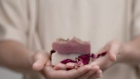 Woman`s hands are holding a bar of rose soap. Closeup is fudgy; while she is moving her hands forward it gets clear. stock video