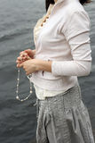Woman's hands holding beads. Young woman wait for somebody. She hold beads in her hands and standing near the water Royalty Free Stock Images