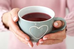 Woman s hands holding big mug with heart . stock images
