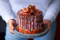 Woman`s hands holding birthday homemade prepared fig cake with chocolate glaze. Decorated with fresh figs on the grey concrete plate Stock Images