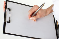 Woman's hands holding blank paper in a clipboard Royalty Free Stock Photo
