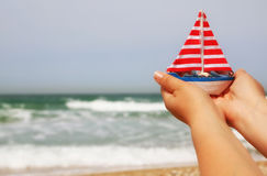 Woman's hands holding a boat in front of sea horizon Royalty Free Stock Photography