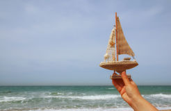 Woman's hands holding a boat in front of sea horizon Royalty Free Stock Image