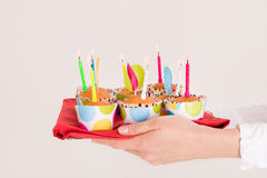 Woman's hands holding a bright tray with muffins and birthday candles. Celebration of a birthday. Royalty Free Stock Images
