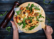 Calzone - Stuffed Pizza with ham, mushrooms, arugula and cheese. royalty free stock image