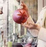 Woman`s hands holding Christmas ornament in shop store. Shopping for holiday decorations