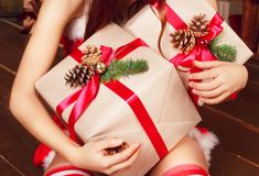 Woman`s hands holding christmas presents in hands sitting near n Royalty Free Stock Photo
