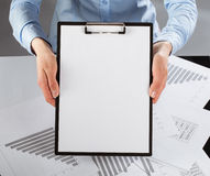 Woman's hands holding clipboard with a blank paper Stock Images