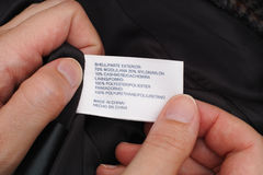 Woman's hands holding clothes label. Stock Photo