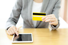 Woman's hands holding a credit card and using tablet pc Royalty Free Stock Images