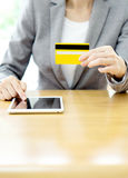 Woman's hands holding a credit card and using tablet pc Royalty Free Stock Image