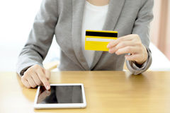 Woman's hands holding a credit card and using tablet pc Stock Images