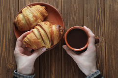 Woman`s hands holding a croissant. And a cup of hot chocolate on a dark background of a wooden table Royalty Free Stock Photo