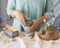 Woman`s hands holding a cup of cocoa over the dinner table, selective focus Royalty Free Stock Images