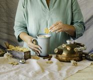 Woman`s hands holding a cup of cocoa over the dinner table, selective focus Stock Photo