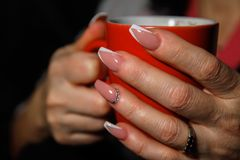 Woman`s hands holding cup of coffee stock photos