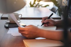 Woman`s hands holding document paper and writing on blank notebook on table in cafe. Closeup image of woman`s hands holding document paper and writing on blank stock photos