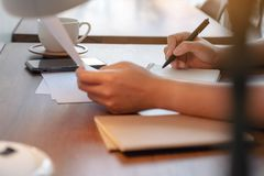Woman`s hands holding document paper and writing on blank notebook on table in cafe. Closeup image of woman`s hands holding document paper and writing on blank stock photo