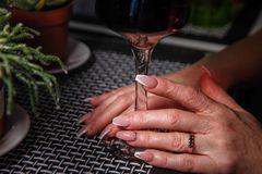 Woman`s hands holding glass of wine stock image