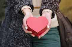 Woman's hands holding a heart shaped box Royalty Free Stock Photography