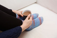 Woman's hands holding a hot beverage, sitting on a couch Stock Image