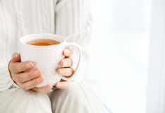 Woman`s hands is holding hot cup of coffee or tea in morning su. Nlight Stock Photo