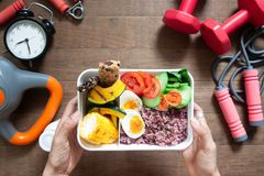 Woman`s hands holding lunch box with rice berry, boiled eggs, sw Stock Photo