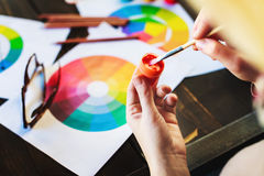 Woman`s hands holding paint, pencils and drawings on table Royalty Free Stock Photography