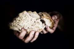 Woman's hands holding a pieces of bread Stock Photography