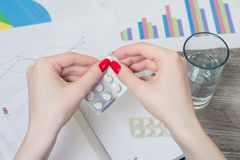 Woman`s hands holding pills. Concept of ill worker royalty free stock photo