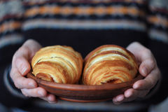 Woman`s hands holding a plate of croissants, selective focus. Background sweater with a jacquard pattern, close-up Stock Photo