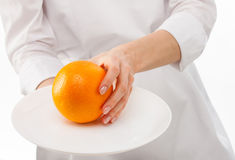 Woman's hands holding ripe orange on a plate Stock Images