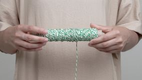 Woman`s hands are holding a roll with white-green string horizontally. The rope hangs down. Than she spins the roll to stock footage