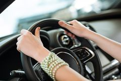 Woman's hands holding on to the wheel of a new car Royalty Free Stock Image