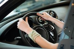 Woman's hands holding on to the wheel of a new car Stock Photography