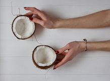 Woman`s Hands holding two coconuts on a white background. Healthy food habits. Raw coconut oil Royalty Free Stock Image