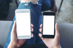 A woman`s hands holding two mobile phones with blank white screen in modern cafe. Mockup image of a woman`s hands holding two mobile phones with blank white Stock Photos