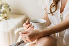 Woman`s hands holding white cup of tea or coffee on light room background. Morning time for breakfast. Bridal morning concept in pastel colors royalty free stock image
