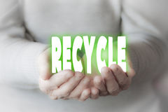 Woman& x27;s hands holding the write & x22;RECYCLE& x22;. Woman& x27;s hands are holding the write & x22;RECYCLE& x22; written with white letters Stock Photos