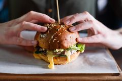 Woman`s hands with hot burger. Fast food concept. Close up view. royalty free stock photography