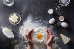 Woman's hands knead dough on table with flour Stock Photos
