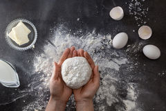 Woman's hands knead dough on table with flour Royalty Free Stock Images