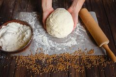 Woman`s hands knead dough. On a table Royalty Free Stock Photo