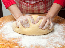 Woman's hands knead dough on wooden table. Female hands in flour closeup kneading dough on table Stock Photography