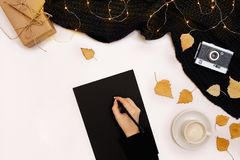 Woman`s hands in a knitted black sweater, holding pen near the blank paper, view from the top. Copy space. Still life. Flat lay Stock Photography