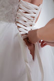 Woman's hands lace up corset on bride's dress Royalty Free Stock Photography