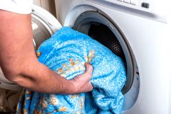 Woman`s hands lays clothes in the washing machine.  stock photos