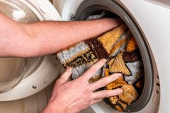 Woman`s hands lays clothes in the washing machine.  stock photo